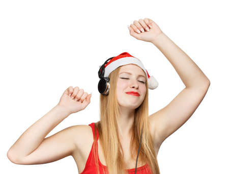 Young woman in santa claus hat and headphones take pleasure from music isolated on white background photo