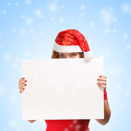 Woman in new year or christmas hat hiding behind the advertisement on blue background with falling snow Stock Photo
