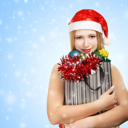 Beautiful young woman in santa claus suit holding box with christmas and new year attributes and gifts on blue snowfall background photo