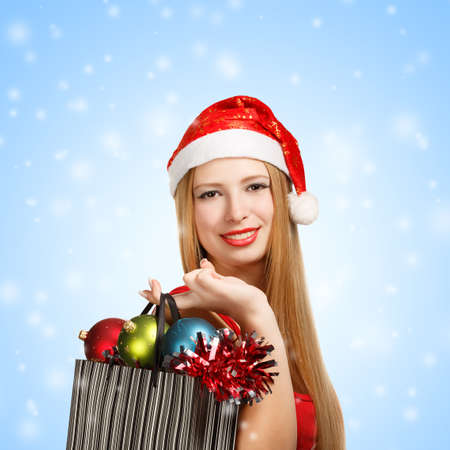 Beautiful young woman in santa claus suit holding box with christmas and new year attributes and gifts on blue snow background photo