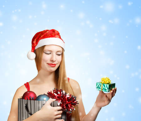Beautiful young woman in santa claus suit holding box with christmas and new year attributes and little gift box on blue snowfall background photo