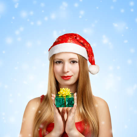 Beautiful young woman in santa claus suit with little gift box on blue snowfall background photo