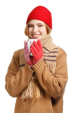 Young smiling woman in brown sweater, buff scarf, red cap and gloves standing with cup isolated on white background photo