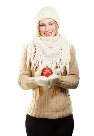 Young beautiful smiling woman in winter clothing with red christmas tree ball photo