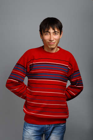 unworried: Man in striped red sweater standing on grey background and smiling with hands behind his back