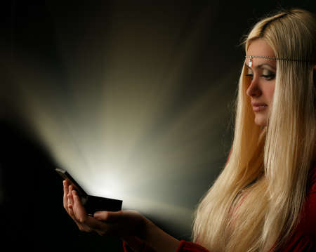 unworried: Beautiful young blonde longhaired woman with glowing box on black background