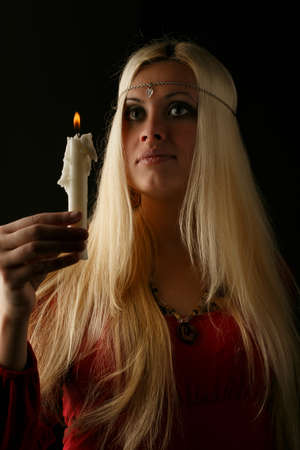 unworried: Beautiful young blonde longhaired woman with candle in her hand isolated on black background