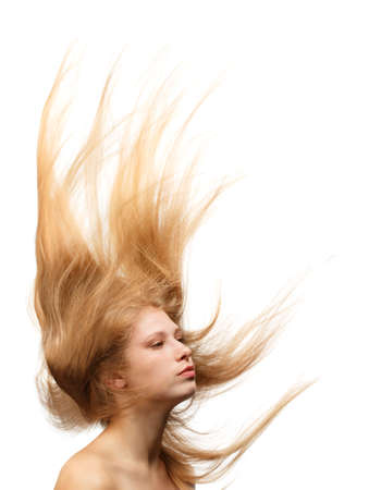 Young beautiful woman with long blond hair flowing like a flame isolated on white background photo