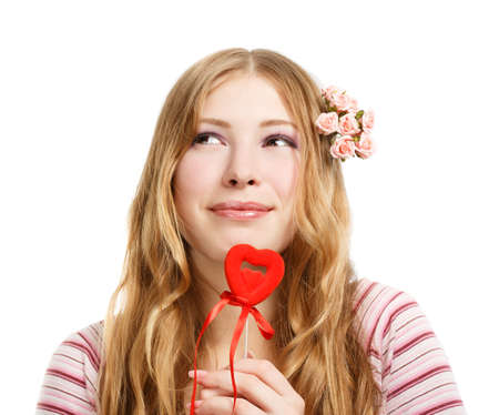 Beautiful young smiling woman in thoughtful pose with red valentine heart isolated on white background