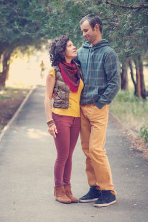 Loving couple in bright clothes walking and hugging together in the park photo