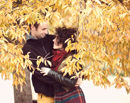 Loving couple in bright clothes hugging in autumnal park photo