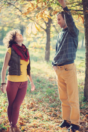 Loving couple in bright clothes walking together and having fun in autumnal park photo