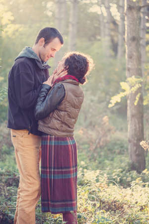 Loving couple in bright clothes hugging together in the park