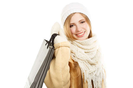 Young smiling woman in warm winter clothing with bag standing isolated on white background photo