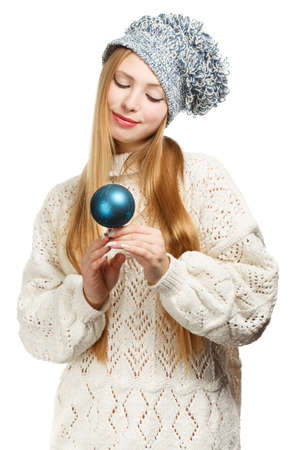 Young beautiful smiling woman in winter clothing and strange hat with blue christmas tree ball photo