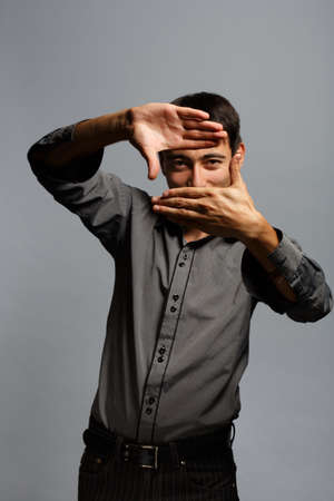 Young business man in shirt with frame gesture on grey background photo