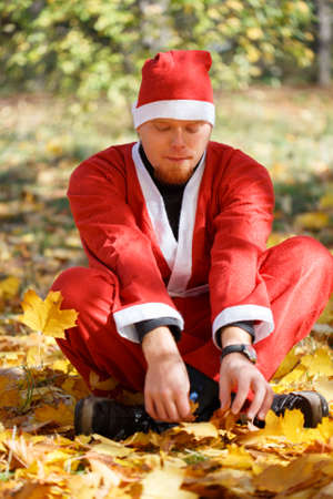 Man in santa claus suit sitting on fallen leaves in autumnal park photo