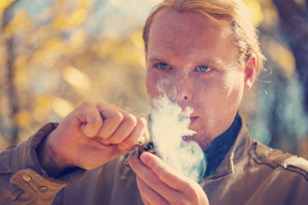 Young beautiful red-haired man smoking tobacco pipe in autumnal park Stock Photo