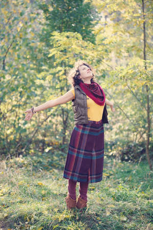 unrestricted: Young beautiful smiling woman in bright clothes standing with open hands in the park Stock Photo