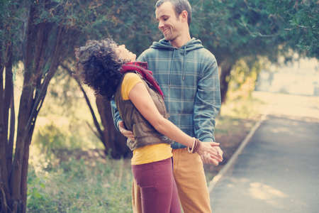 emotional couple: Loving couple in bright clothes dancing on the park alley Stock Photo