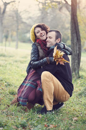 Loving couple in bright clothes hugging each other sitting at the grass in the park Stock Photo