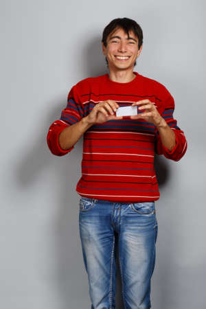Smiling man in red striped sweater on gray background with business card photo