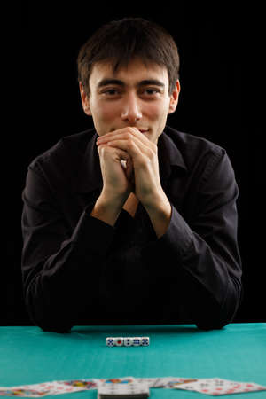 Beautiful young gambler man in black shirt sitting at the playing table isolated on black background photo