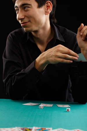 trickster: Beautiful young gambler man in black shirt sitting at the playing table gets a card from his sleeve isolated on black background