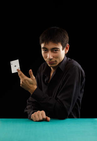 Beautiful young gambler man in black shirt sitting at the playing table with ace of spades in his hand isolated on black background photo