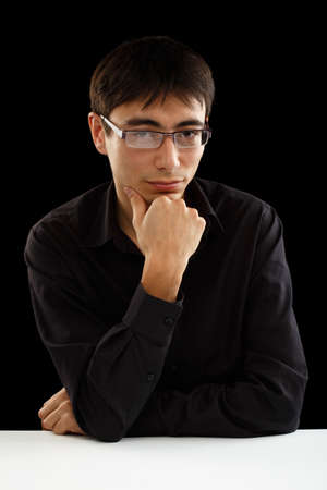 Beautiful young man in black shirt and glasses sitting at the table in thoughtful pose isolated on black background photo