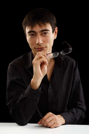unworried: Beautiful young man in black shirt and glasses sitting at the table in thoughtful pose isolated on black background Stock Photo