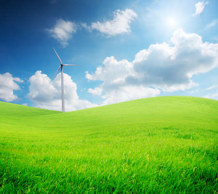 Wind turbine standing on green grass field under blue cloudy sky with sunlight photo