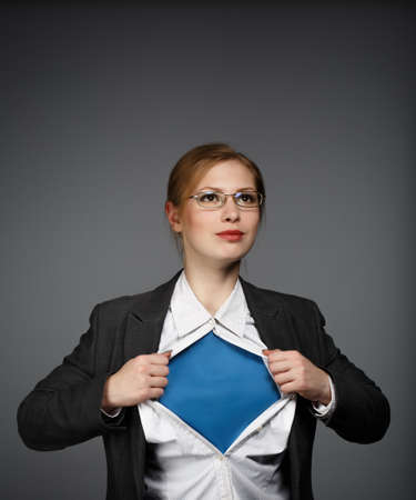 superwoman: Joven y bella mujer en traje de negocios y gafas sobre fondo gris