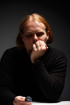 Young red-haired man in black sweater sitting on grey gradient background under dramatic light in thoughtful pose holding poker chip photo
