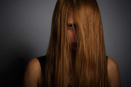 tousled: Young woman with long blonde hair standing in dramatic light and angry looking through locks on grey background