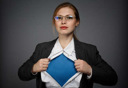 아름다운 젊은 비즈니스 정장에서 여자와 회색 배경에 슈퍼맨 개념 안경 스톡 콘텐츠
