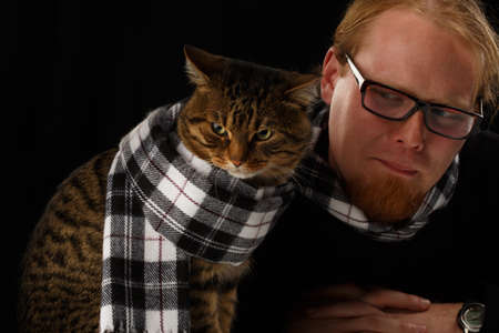 Relaxed man sitting with cat in his scarf  Shallow DOF  Focus on cat  Stock Photo