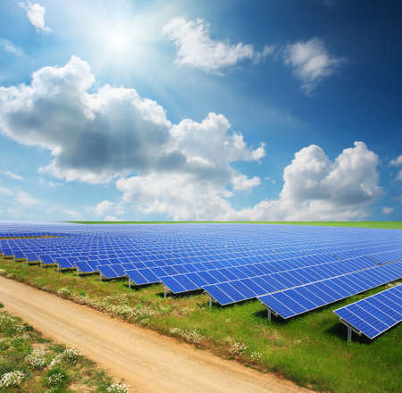 Solar panels with green field and country road photo