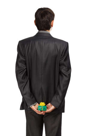 gift behind back: Man in business suit hide a gift behind back isolated on white background Stock Photo