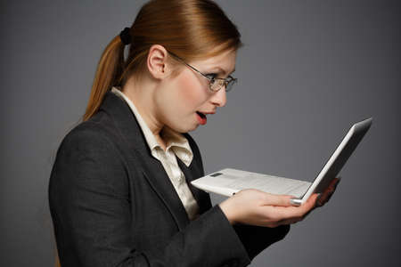 netbook: Beautiful young woman in business suit and glasses with surprised face holding white netbook on grey background