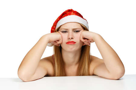 wearied: Young woman in santa claus hat posing isolated on white background with scowl look Stock Photo