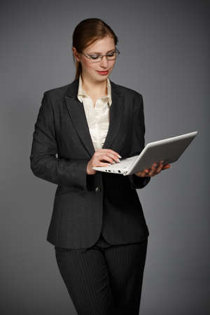Beautiful young woman in business suit and shirt holding white notebook or pad on grey background Stock Photo