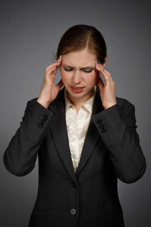 Businesswoman with strong migraine on gray background