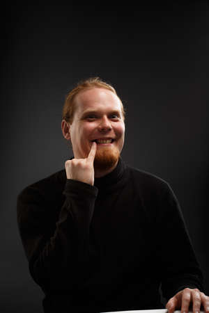 Beautiful young smiling red-haired bearded man in black sweater with Dr Evil gesture on grey background