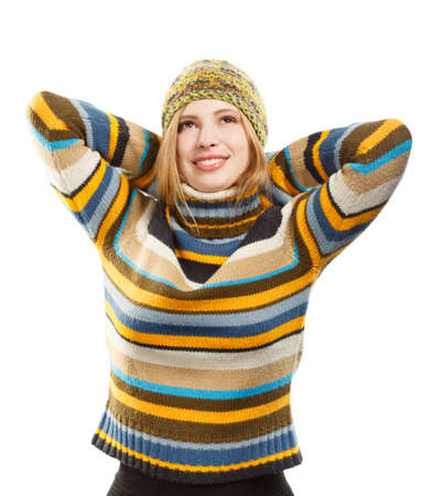 arms behind head: Beautiful thoughtful smiling young woman in knitted striped sweater and hat with arms behind head and dreamy face gesture standing isolated on white background