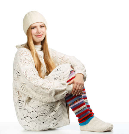 gaiters: Young beautiful smiling woman with long blonde hair siting in white knitted sweater, cap and striped gaiters isolated on white background Stock Photo