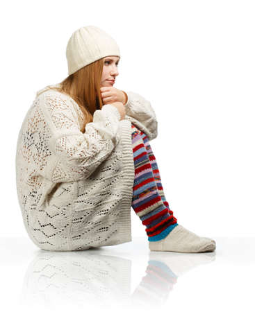 gaiters: Young beautiful thoughtful woman with long blonde hair siting in white knitted sweater, cap and striped gaiters isolated on white background