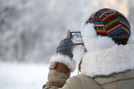 Women in winter clothing, fingerless mittens and ornamented hat photographing snowy forest by a mobile phone. Shallow dof. Focus on hand. Stock Photo
