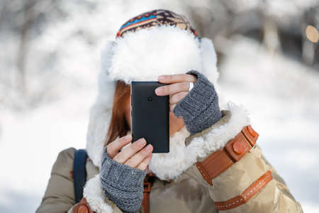Women in winter clothing, fingerless mittens and ornamented hat with white fur photographing snowy landscape by a mobile phone. Shallow dof. Focus on hands. Stock Photo