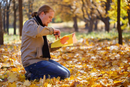 sitting on the ground: Young red-haired man sitting on the ground spangled with leaves in autumn park cutting maple leaves of colored paper by scissors